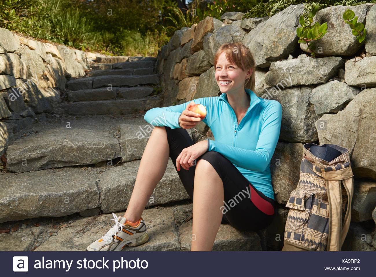 Mitte Erwachsene weibliche Läufer Pause eine im Park Essen eines Apfels Stockbild