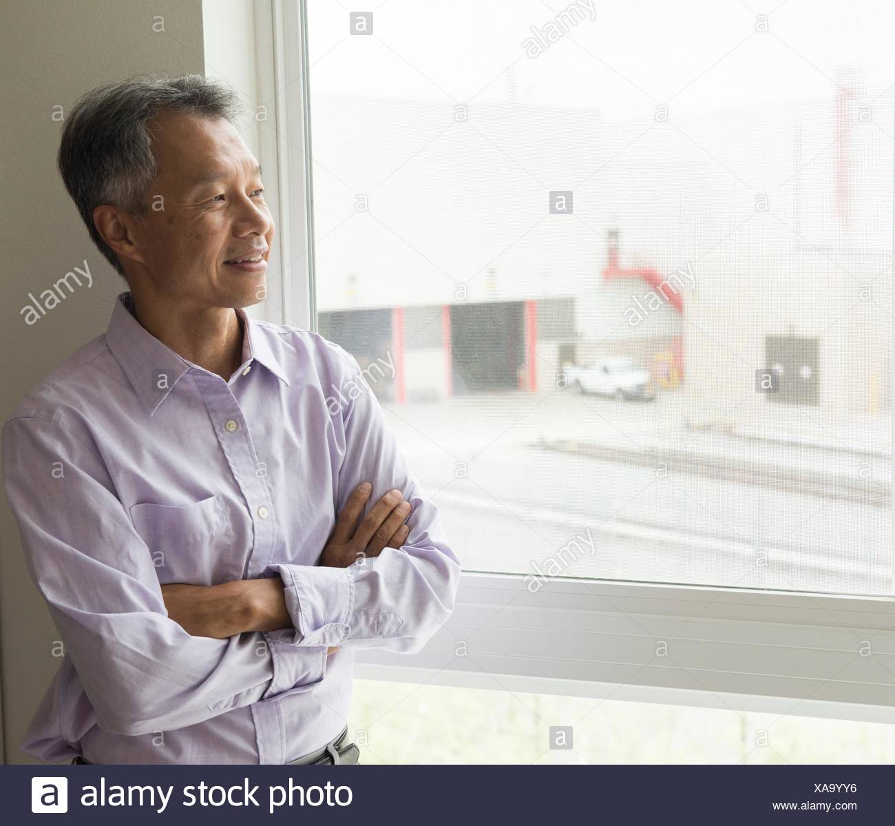 Taille bis des reifen Mannes Blick aus Fenster Arme gekreuzt Stockbild