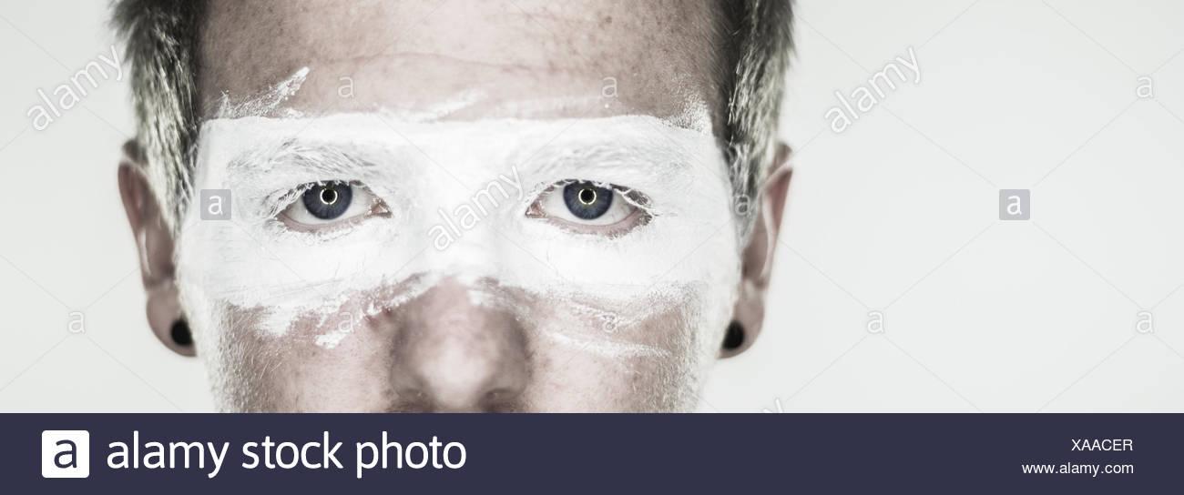 Studioaufnahme des Mannes Gesicht mit bemalten Brille Stockbild