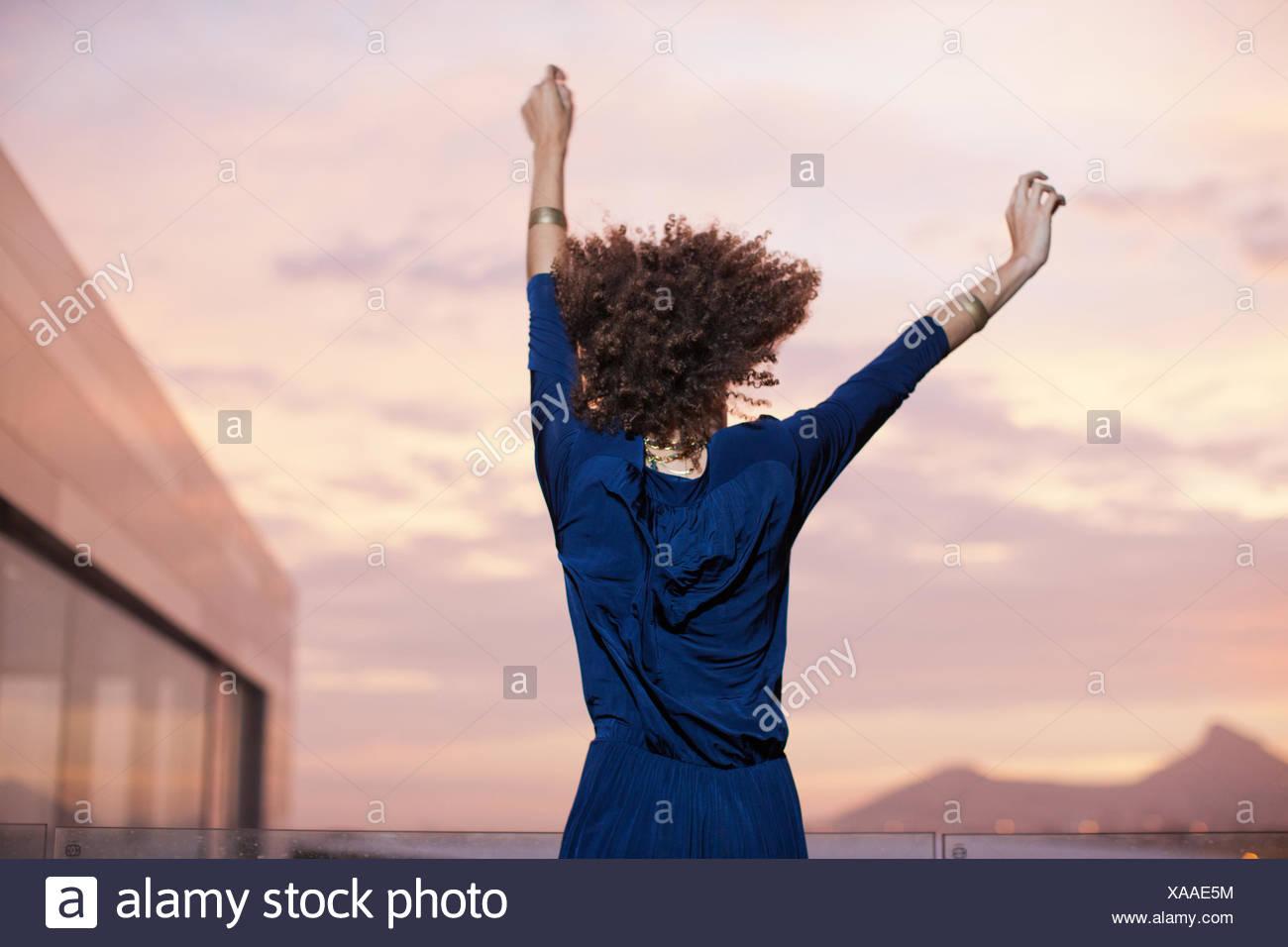 Frau tanzt mit erhobenen Armen Stockbild