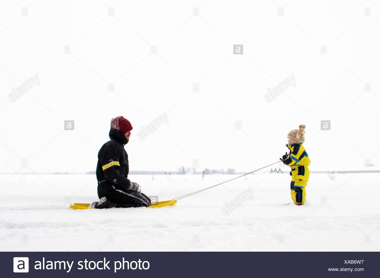 Sohn zieht Vater auf Schlitten (2-3 Jahre) Stockfoto