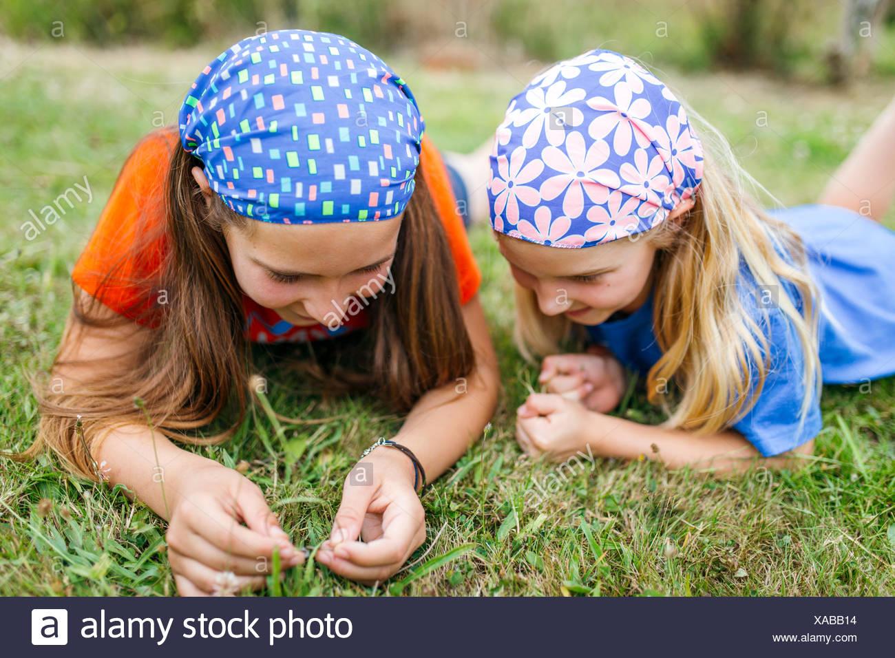 Zwei kleine Schwestern auf einer Wiese liegend Stockbild