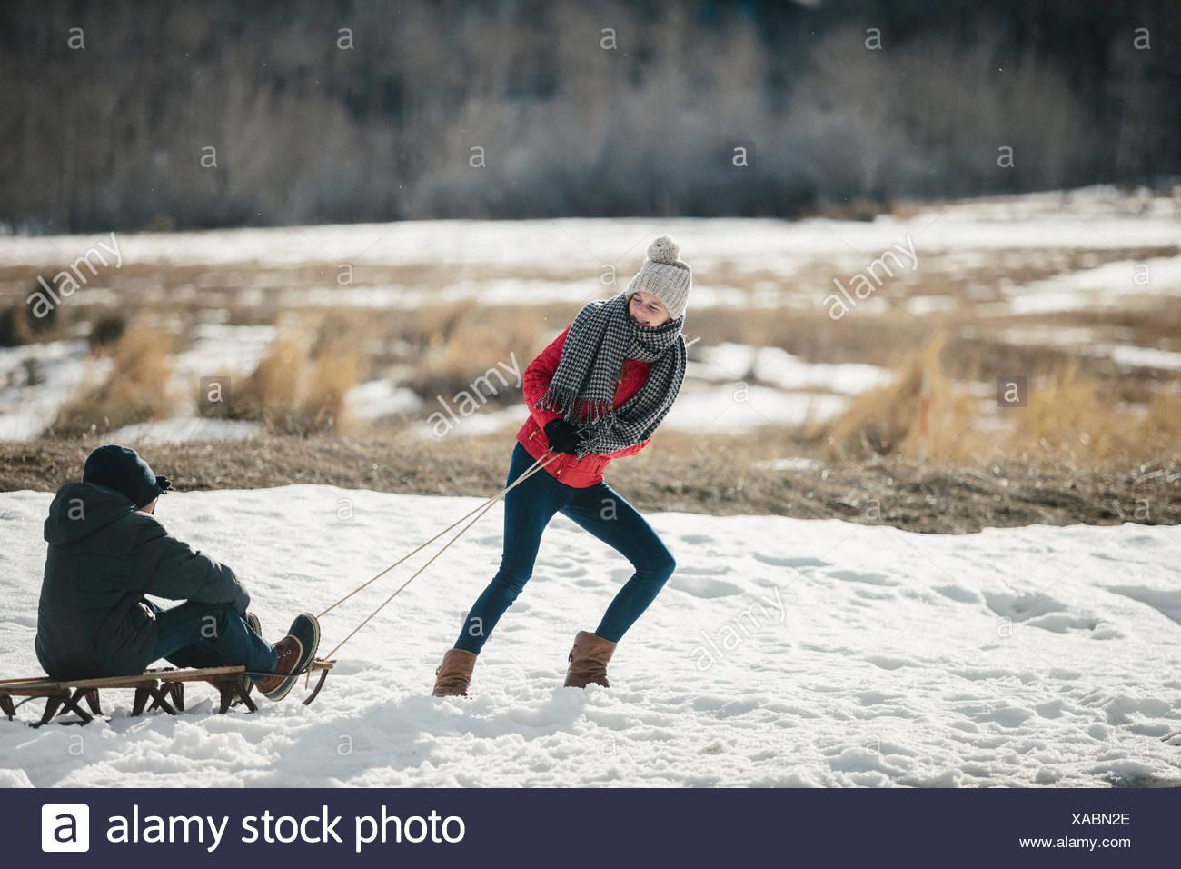 Bruder und Schwester im Schnee, einer den anderen auf einem Schlitten ziehen. Stockfoto