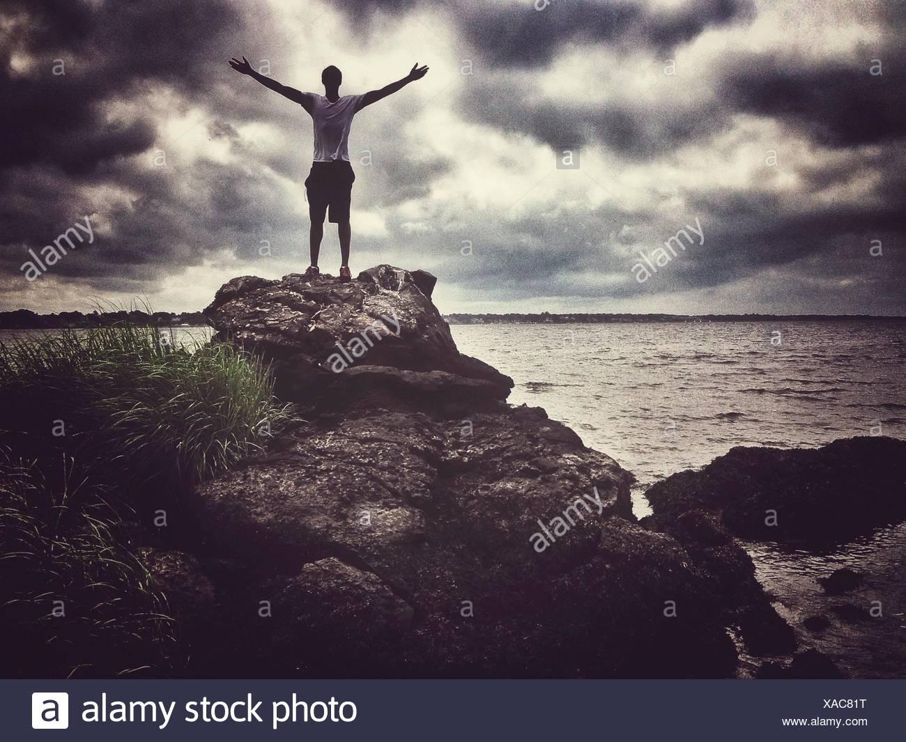 Mann mit Arme ausgestreckt auf Felsen gegen Wolken Himmel Stockfoto