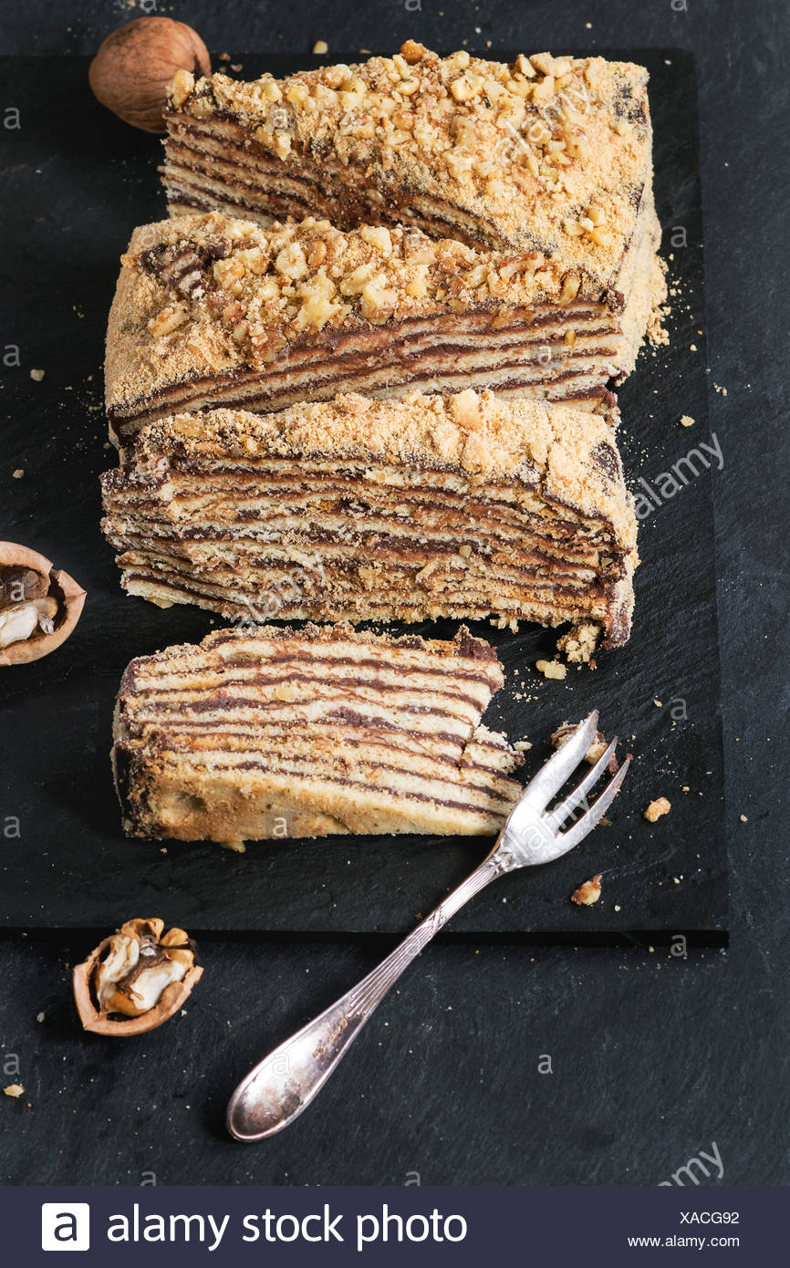 In Scheiben geschnitten hausgemachte Honigkuchen mit Schokolade Creme und Walnüsse, serviert mit Dessertgabel und gehackten Nüssen auf Schiefer Tafel. Nach oben Stockfoto