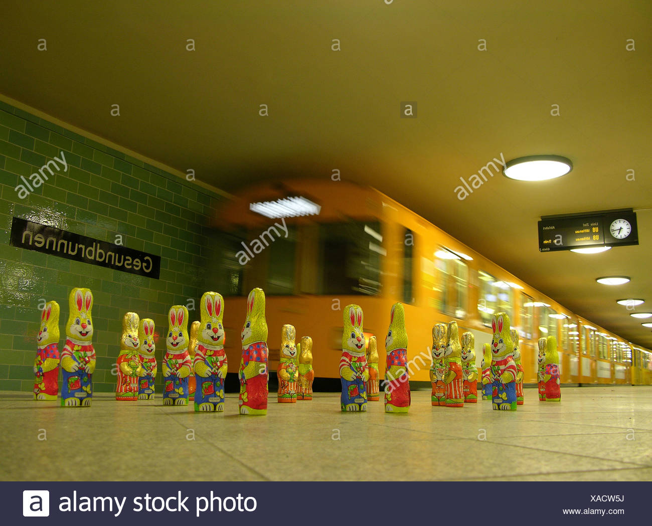 Eine Gruppe von Osterhasen aus Schokolade stehen auf einer u-Bahn-Plattform vor einer ankommenden u-Bahn U Gesundbrunnen Stockbild