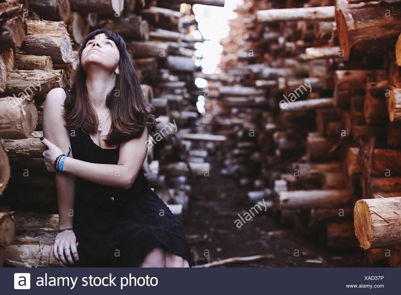 Frau sitzt im Wald auf der Suche, Arme im Freien halten Stockbild