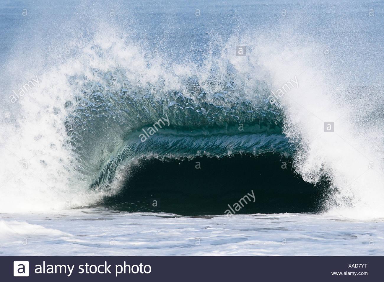 Eine große Welle bricht mit Gewalt über eine flache Sandbank. Stockbild