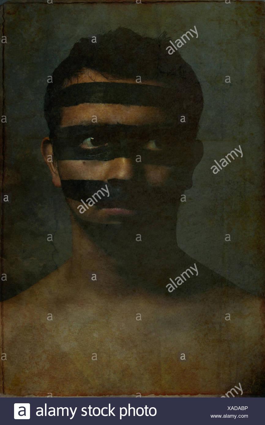 Porträt des jungen Mannes mit schwarzen Streifen über sein Gesicht Stockfoto