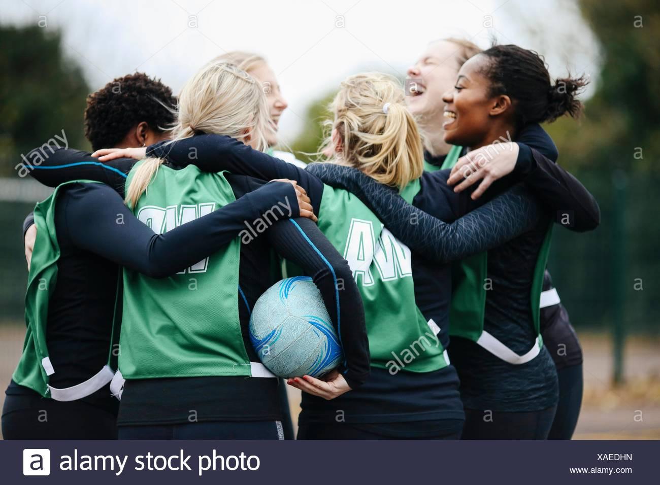 Weibliche Netball Team feiern im Huddle auf Korbball Gericht Stockfoto