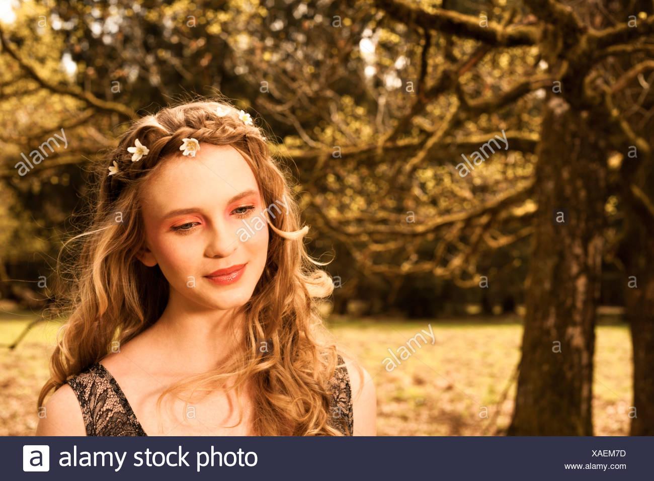 Porträt von Tagträumen junge Frau mit Blumen im Haar Stockbild