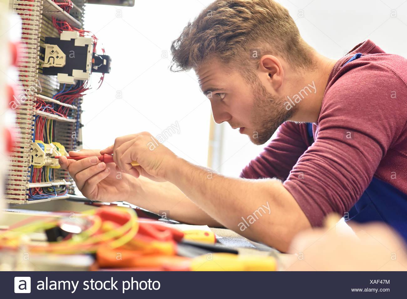 Elektriker-Schüler arbeiten am Schaltschrank Stockbild