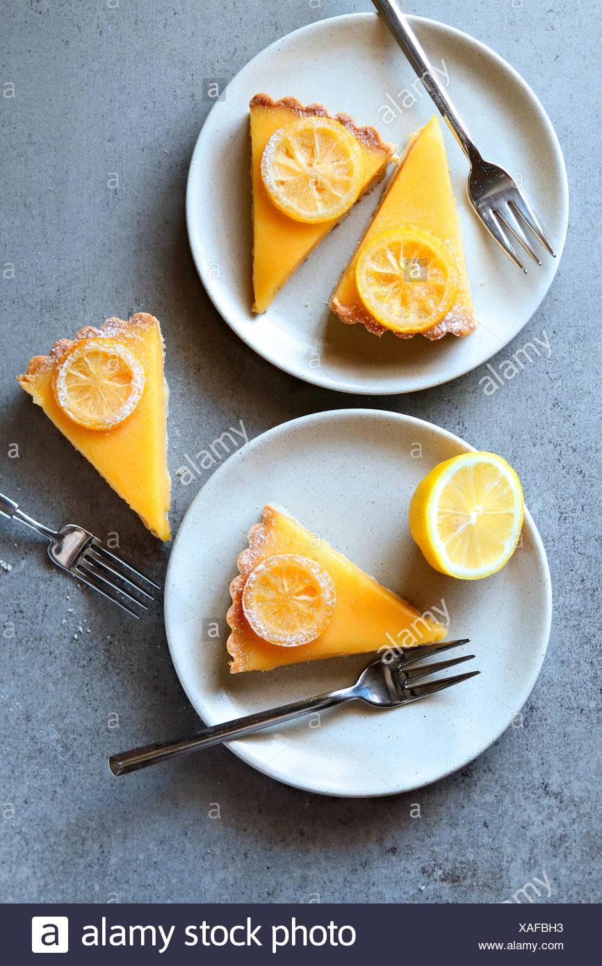 Herbe Zitronenscheiben auf weißen Tellern serviert. Ansicht von oben Stockbild