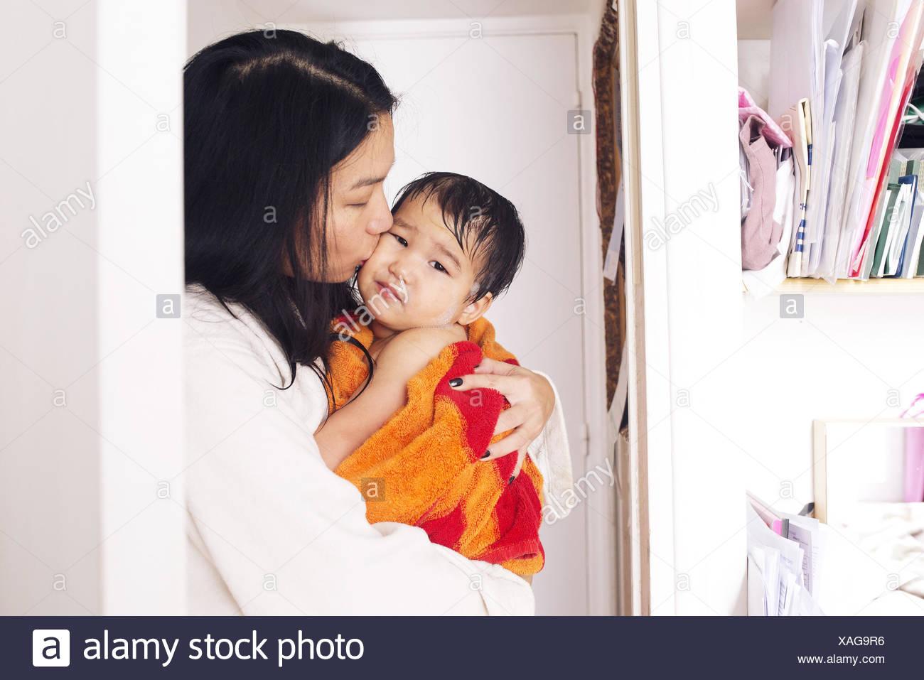 Mutter tröstlich jungen Sohn nach einem Bad Stockbild