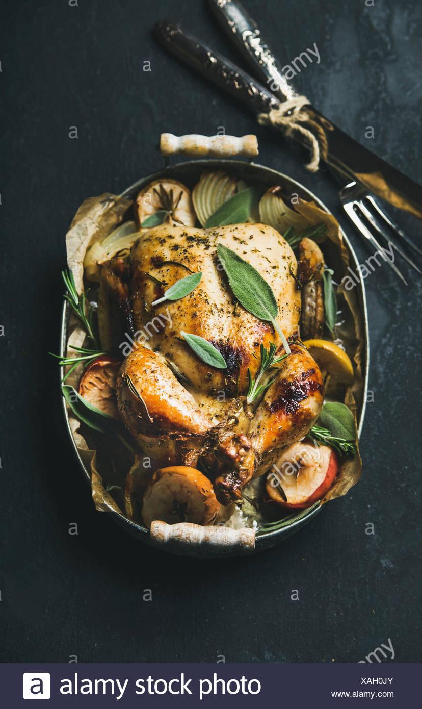 Ofen gebratenes ganzes Huhn mit Zwiebeln, Äpfel und Salbei in Serviertablett mit Besteck über dunklem Stein, Ansicht von oben, wählen Sie Stockbild