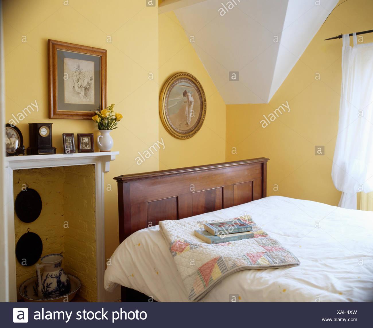 Bilder An Der Wand Uber Dem Dunklen Holz Bett Mit Weissen Bettdecke Im Dachgeschoss Schlafzimmer Mit Kamin Stockfotografie Alamy