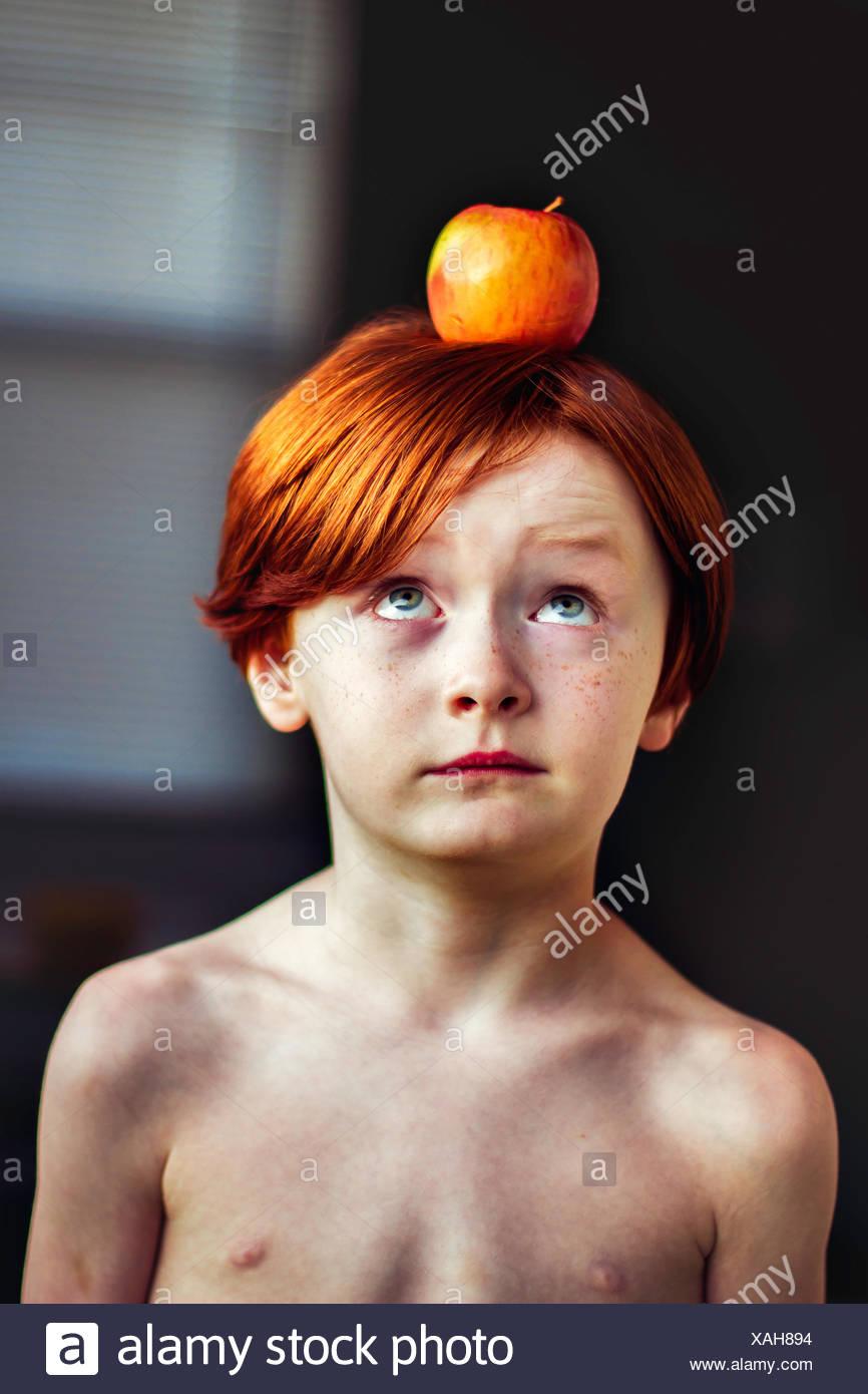 Junge, einen Apfel auf dem Kopf balancieren Stockbild