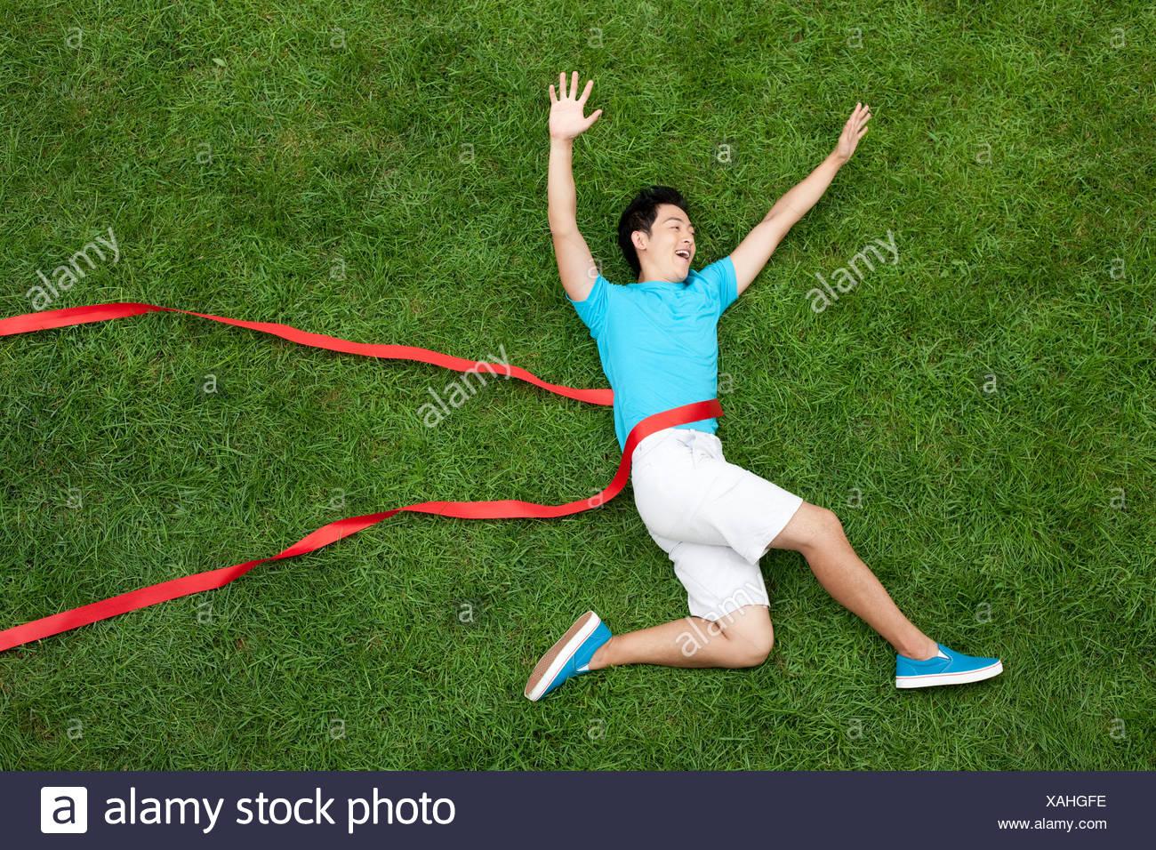 Kreative junge Mann imitieren ausgeführten Angriff auf Rasen Stockbild
