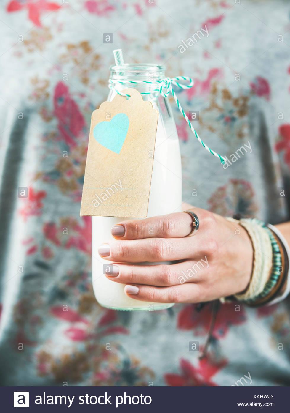 Junge Frau in graues T-shirt mit Blumenmuster Flasche milchfreien Mandelmilch in der Hand halten. Sauber, Essen, Vegan, vegetarisch, Diät, Gesundheit Stockbild