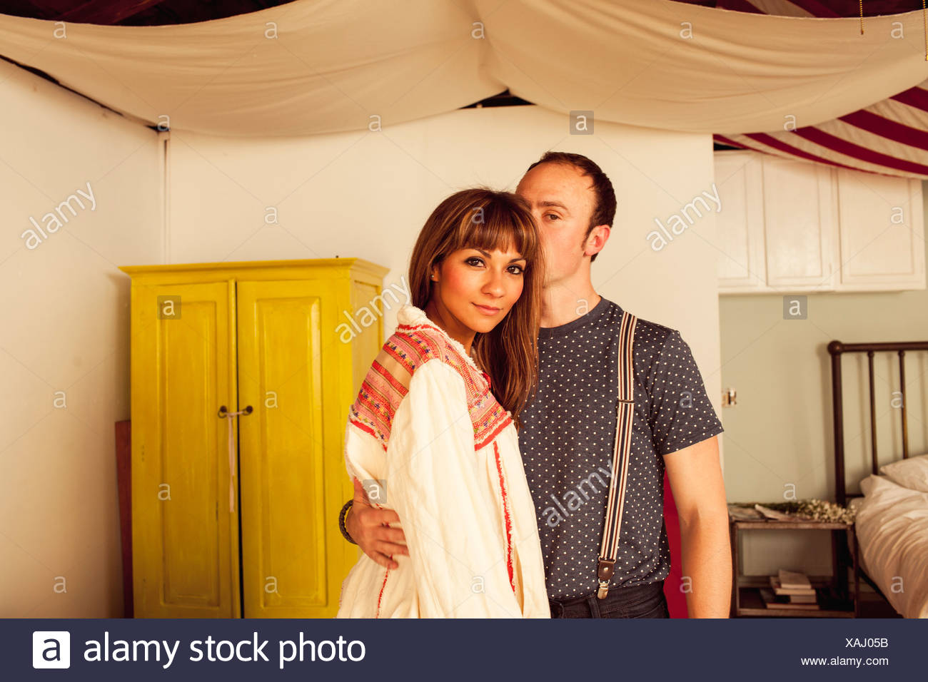 Mann mit Arm um Frau im Schlafzimmer Stockbild