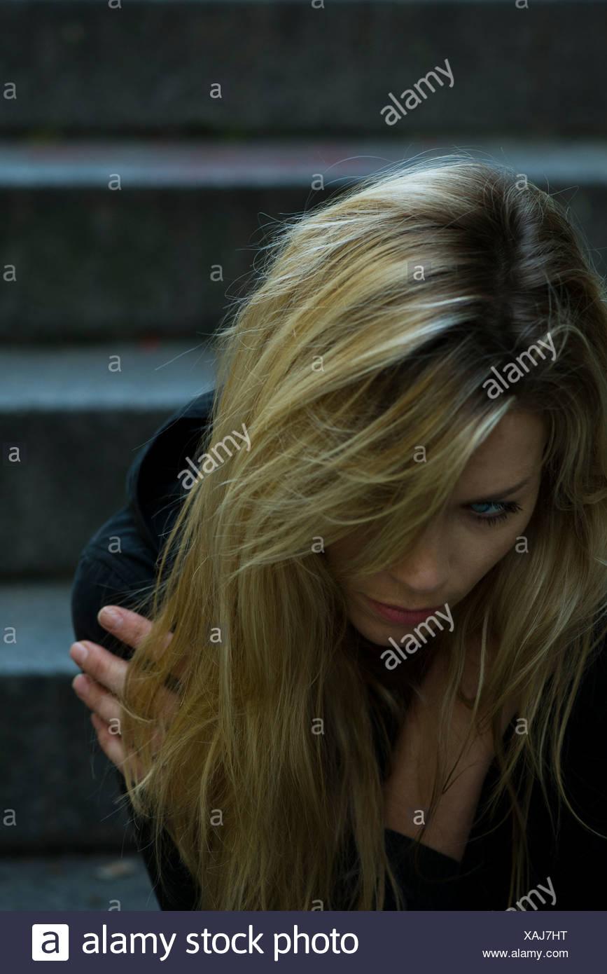 Frau sitzt alleine auf Schritte Stockbild