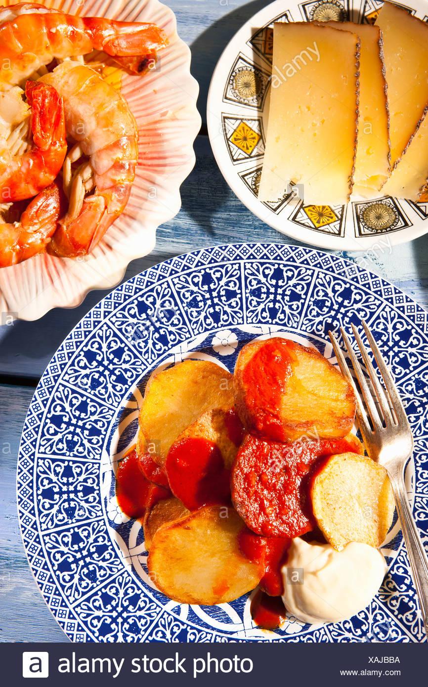 Platten mit Käse, Garnelen und Kartoffeln Stockbild