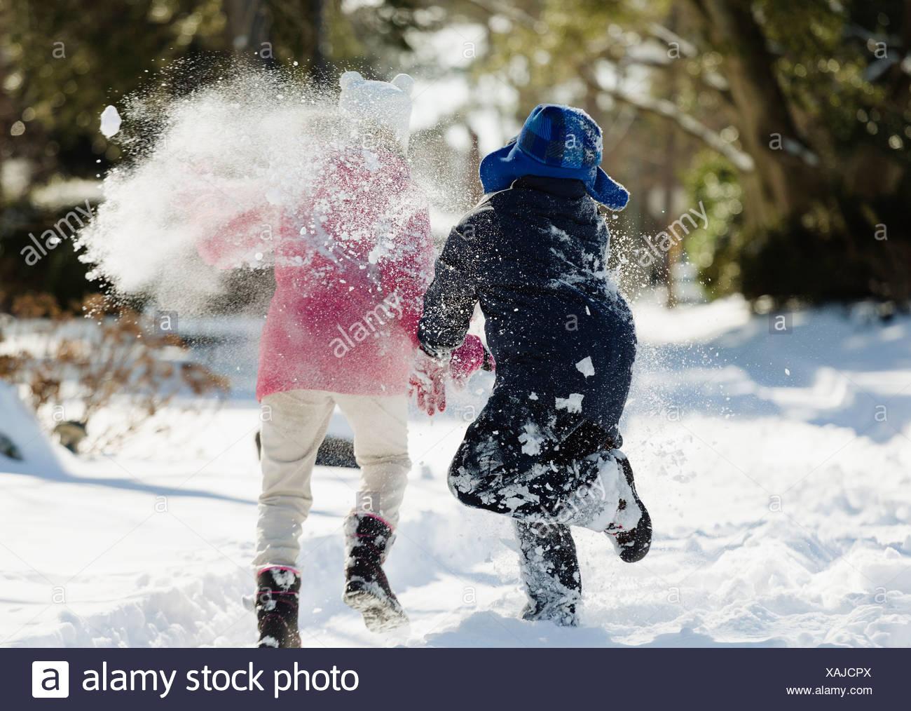 Zwei Kinder laufen im Schnee Stockbild