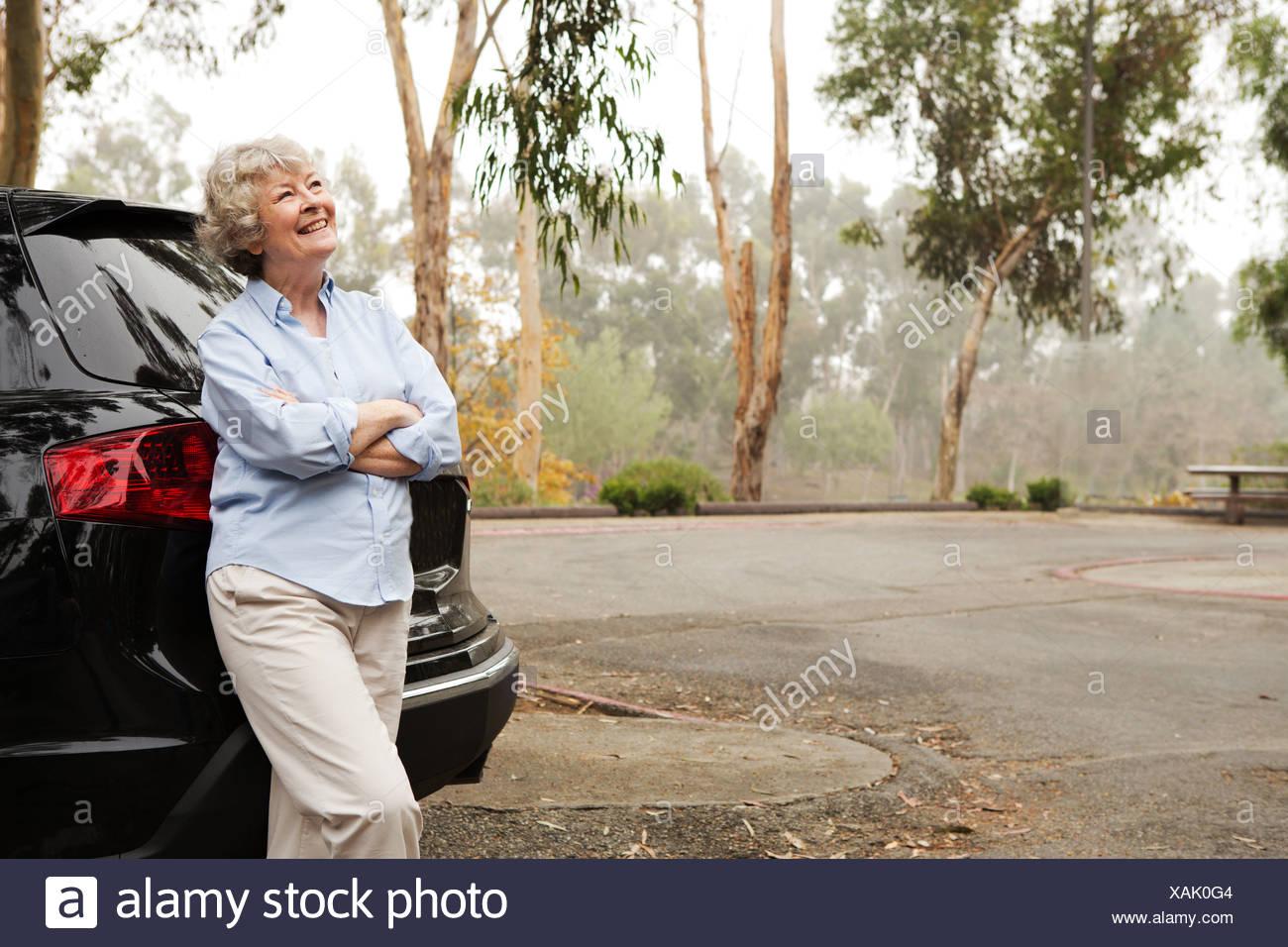 Senior Frau stehend gegen Heck schwarz Stockfoto