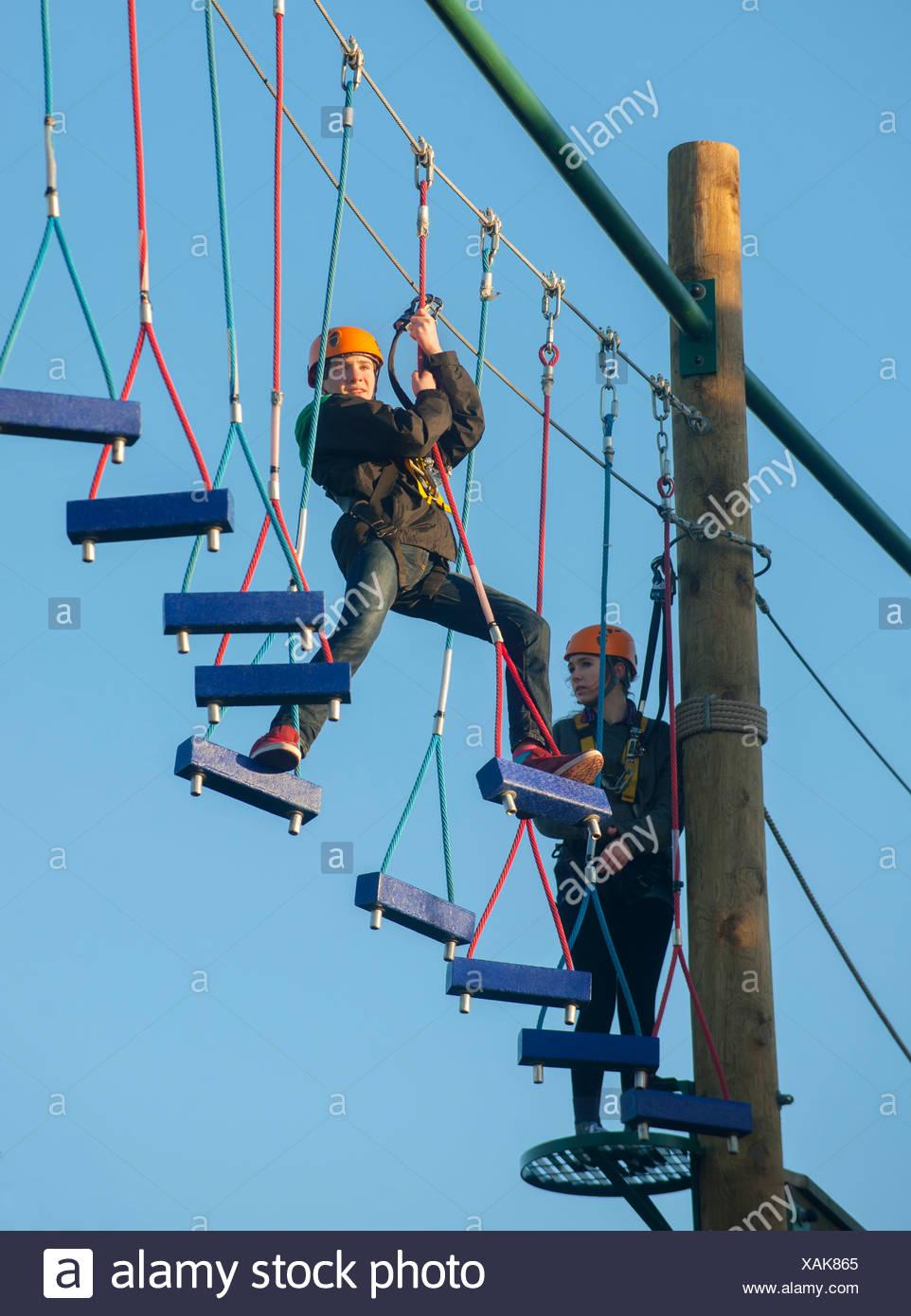 Klettern am Hindernis-Parcours im Teenageralter Stockbild