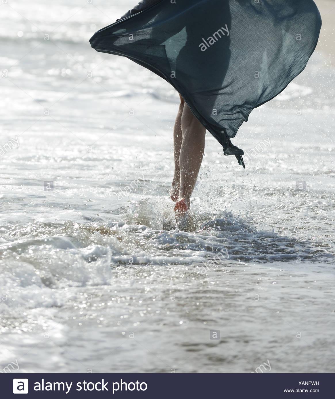 Eine junge Frau zu Fuß auf das Meer Stockbild