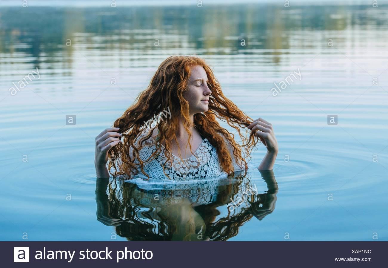 Kopf und Schultern der schöne junge Frau mit langen roten Haaren in See Stockbild
