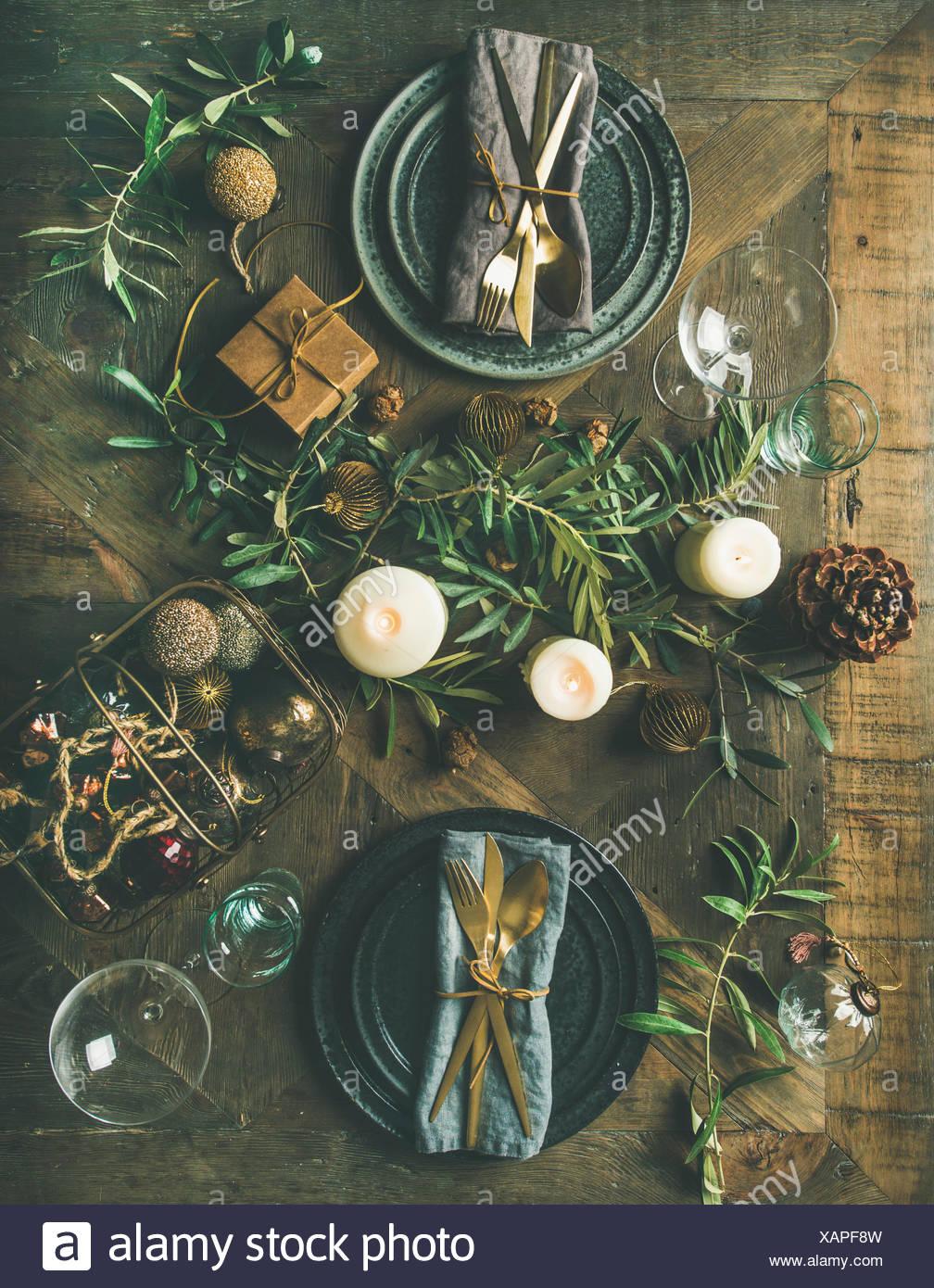 Weihnachten oder Silvester Urlaub Tabelle einstellen. Flachbild-lay von Teller, Besteck, Gläser, Kerzen, Olivenzweige und Spielzeug festliche Dekorationen über Stockbild