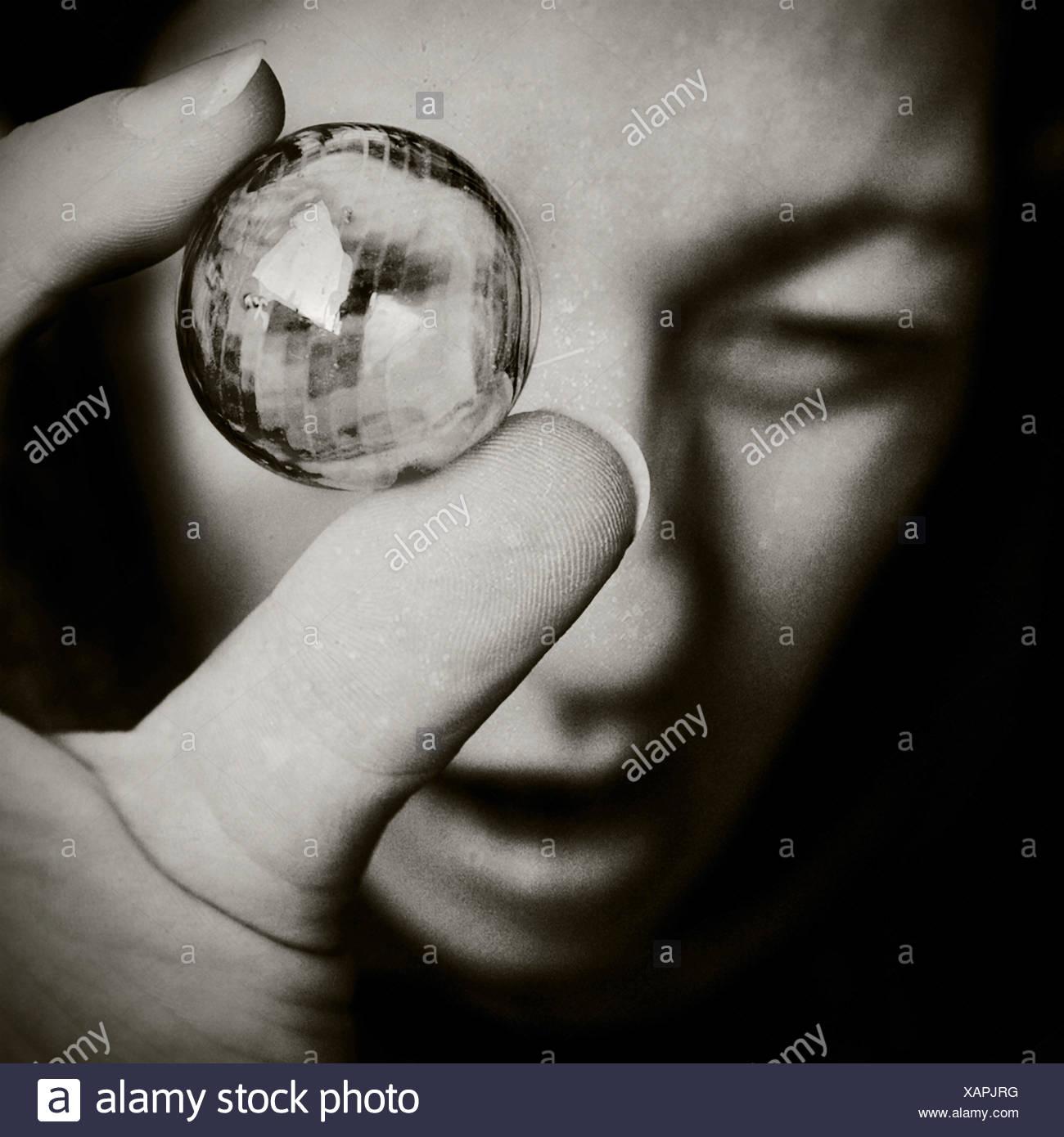 Nahaufnahme eines Mädchens hält eine Glasperle Stockbild