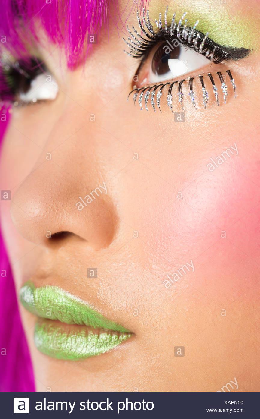 Extreme junge funky Frau Gesicht falsche Wimpern grünen Lippenstift Stockbild