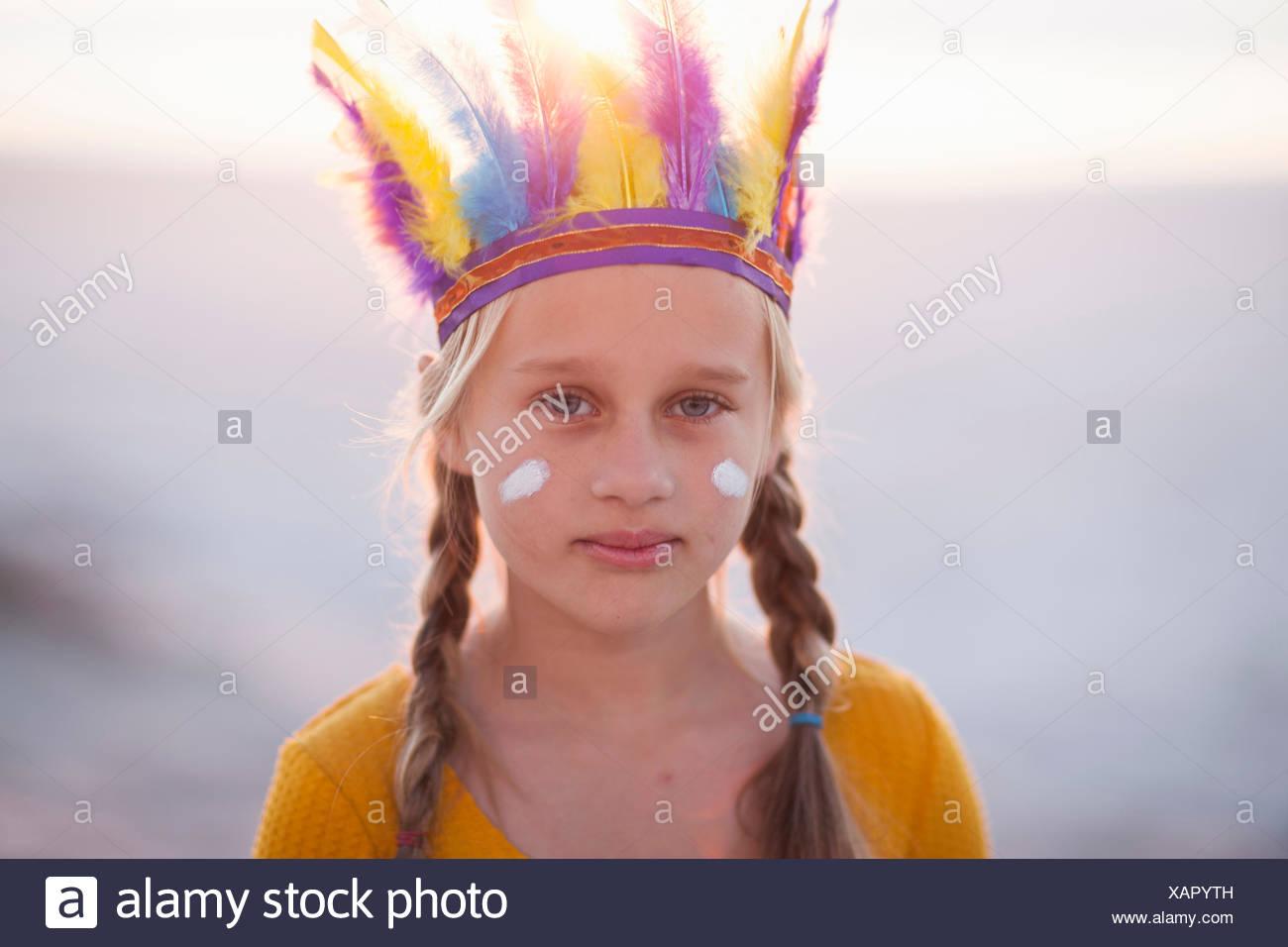 Porträt von Mädchen verkleidet als Indianer mit Feder Kopfschmuck Stockbild