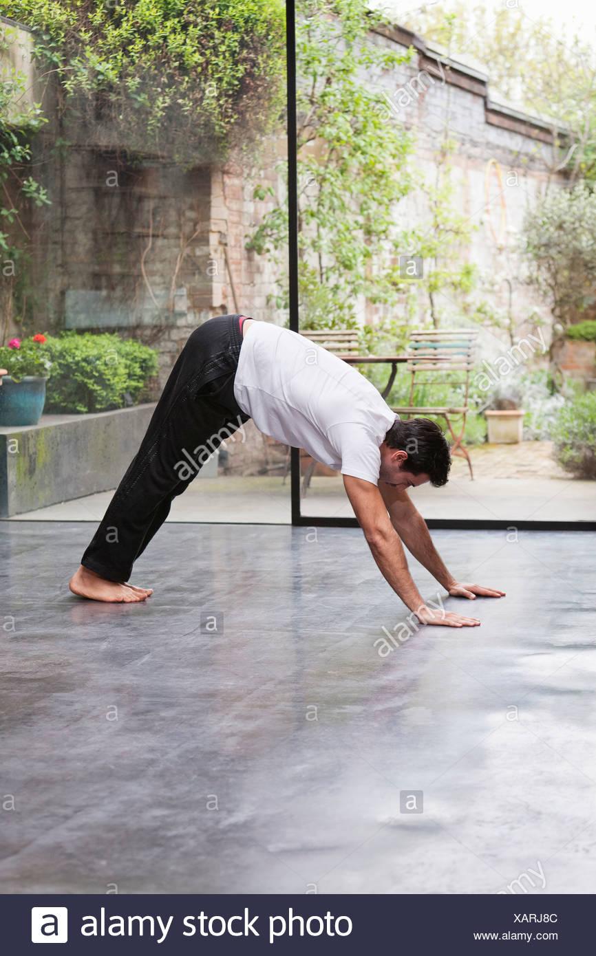 Mann unten Hund-Yoga-Pose zu üben Stockbild