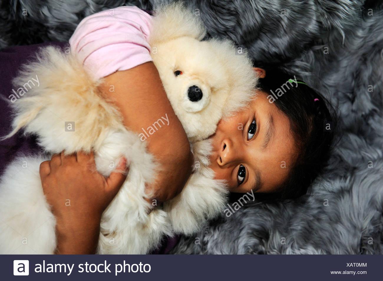 Mädchen mit indigenen Gesichtszüge umarmt einen Teddybären, Stofftiere und Teppiche aus Alpaka Fell in einer kleinen Familie Stockbild