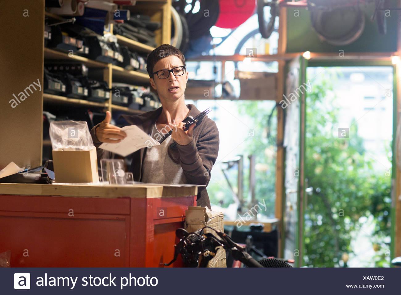 Frau am Schalter im Fahrradwerkstatt holding Fahrrad Teil und Papierkram Stockbild