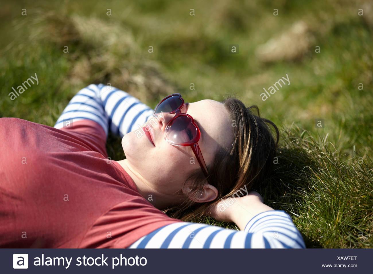 Junge Frau mit Herz Form Sonnenbrille liegen auf dem Rasen Stockbild