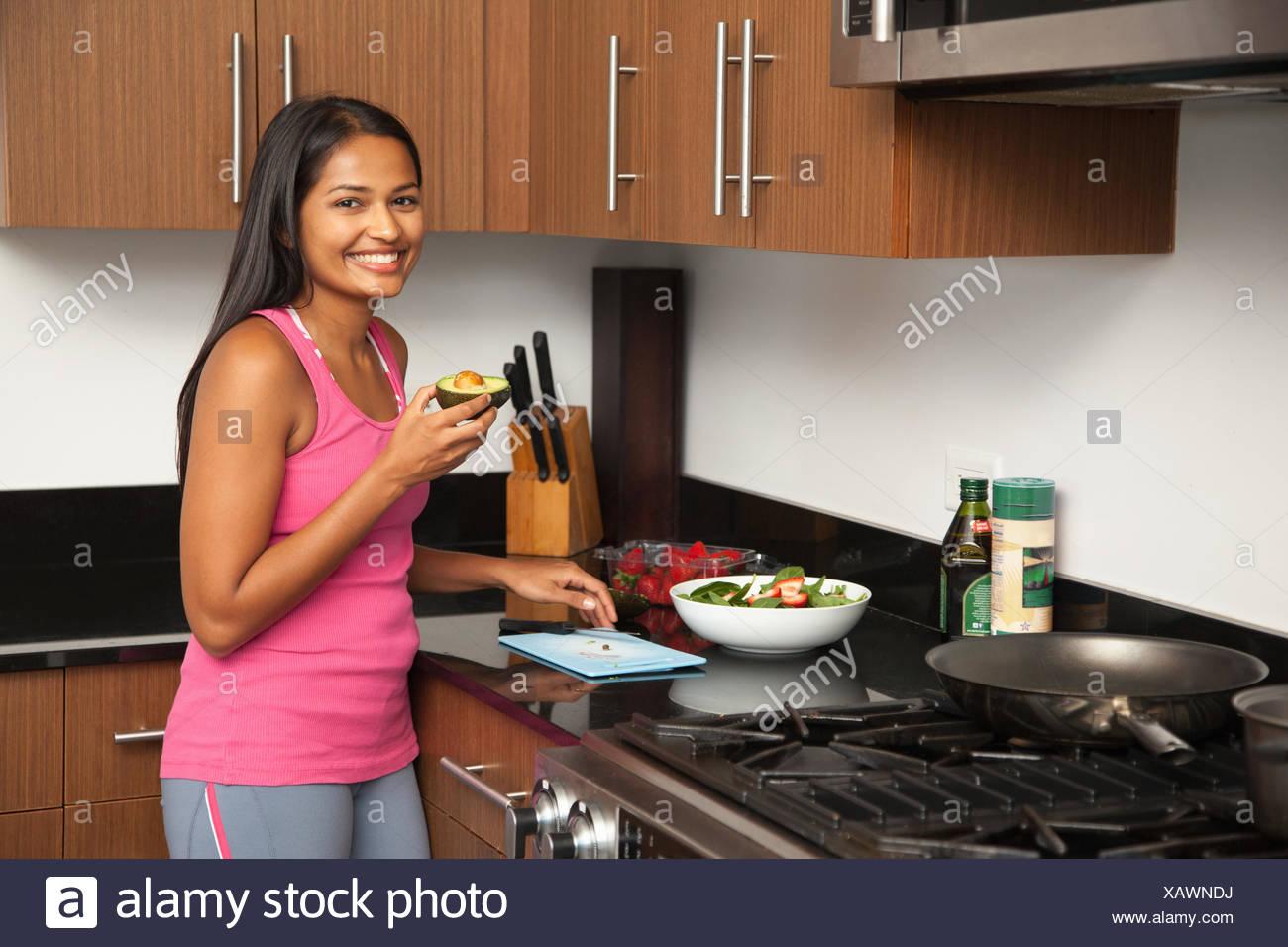 Frau bereitet Salat in Küche Stockbild