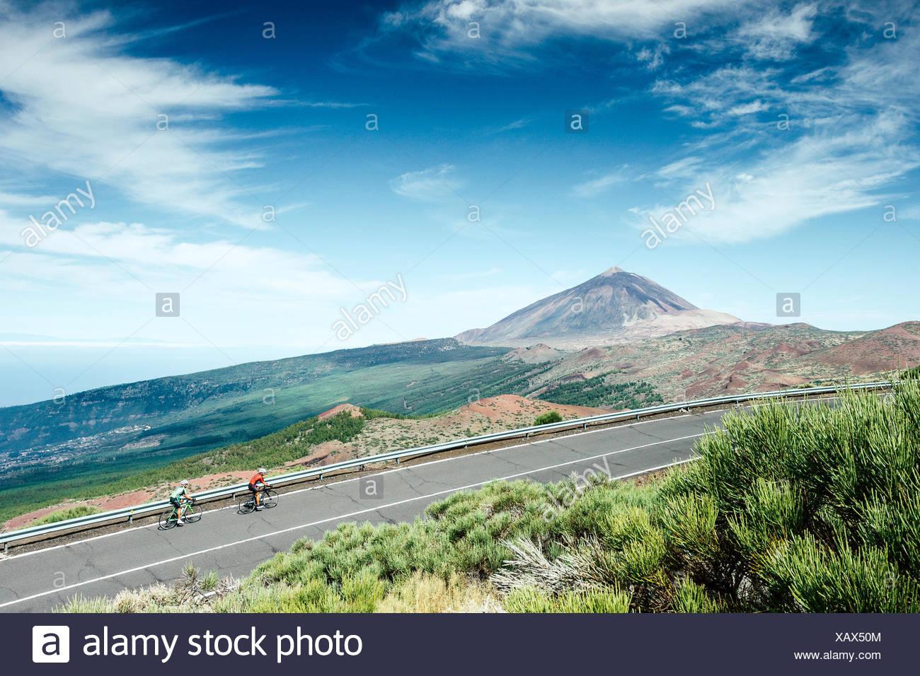 Zwei Radfahrer radeln auf Mountain Road mit Teide im Hintergrund Mount, Nationalpark Teide, Teneriffa, Kanarische Inseln, Spanien Stockfoto
