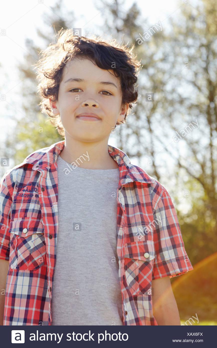 Jungen tragen überprüft Shirt im park Stockbild