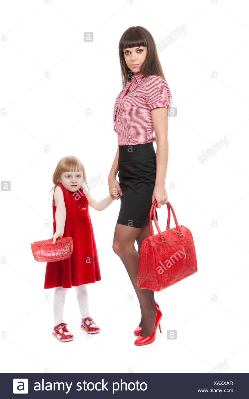 b26e09a590917 Modische Mom in roten Schuhen und ihrer kleinen Tochter mit einer schönen  Handtasche Stockbild