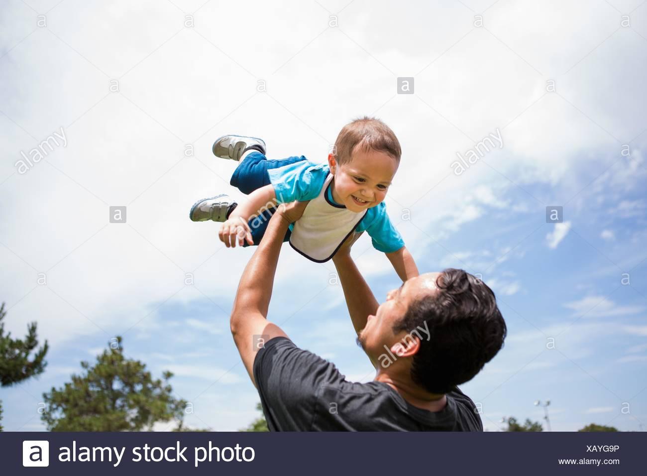 Junger Mann hob Kleinkind Bruder im Park zu spielen Stockbild