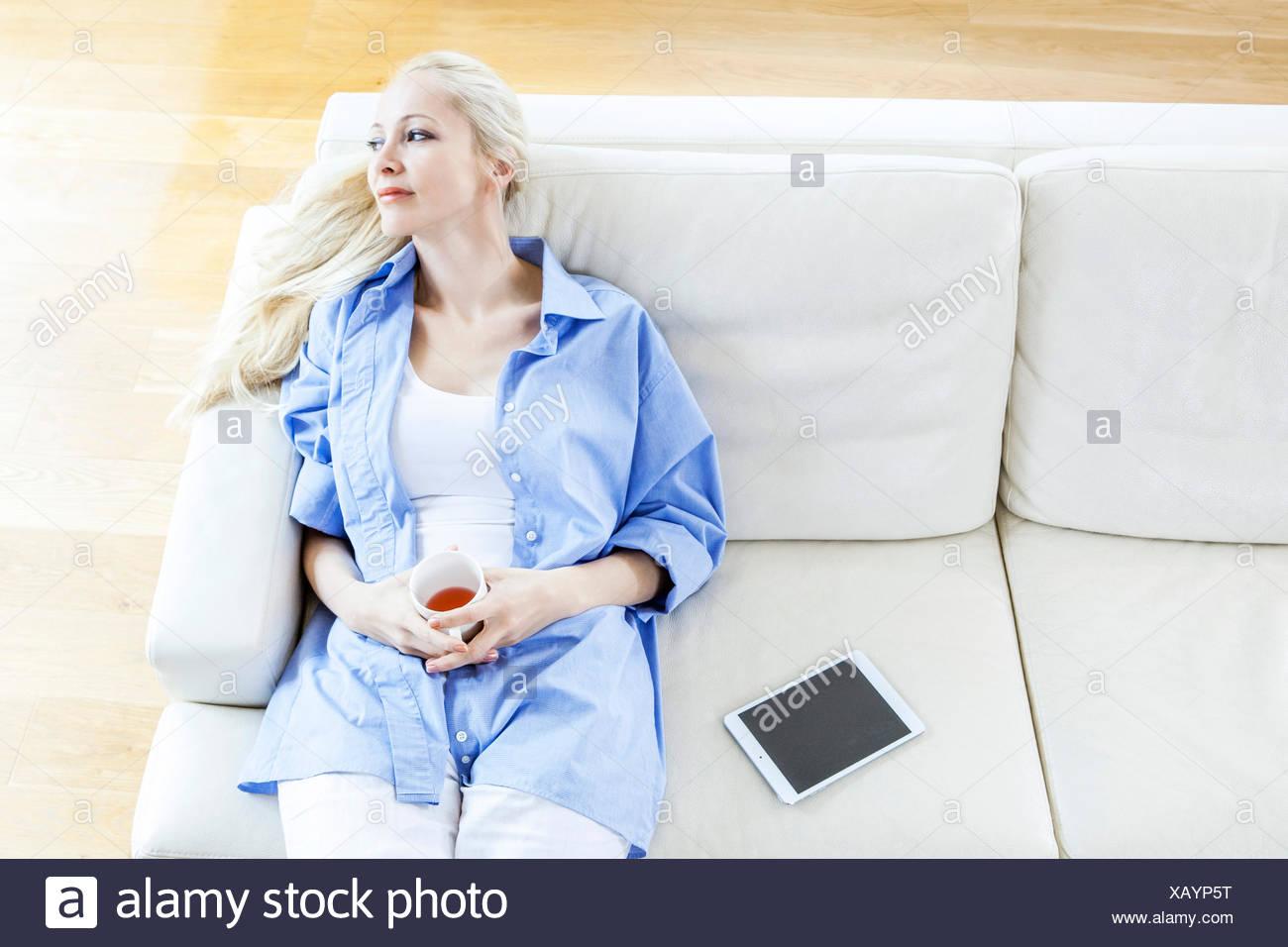 Blonde Frau sitzt auf dem Sofa Tagträumen Stockbild