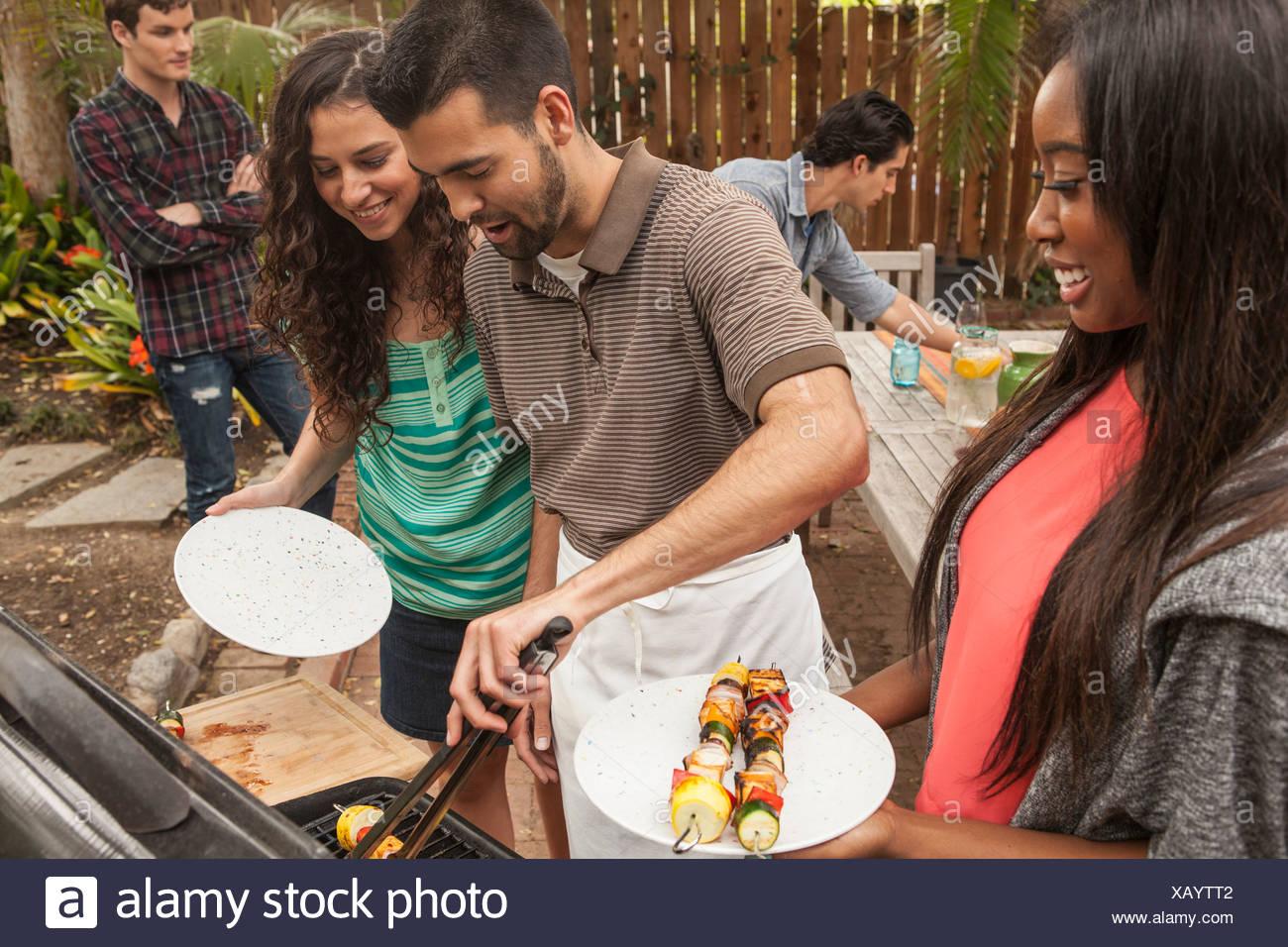 Freunde an Tisch Grill Essen teilen Stockbild