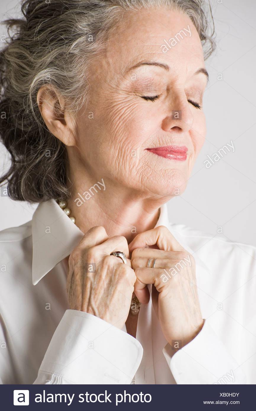 Porträt der älteren Frau, die Hände auf Kragen, Augen geschlossen Stockbild