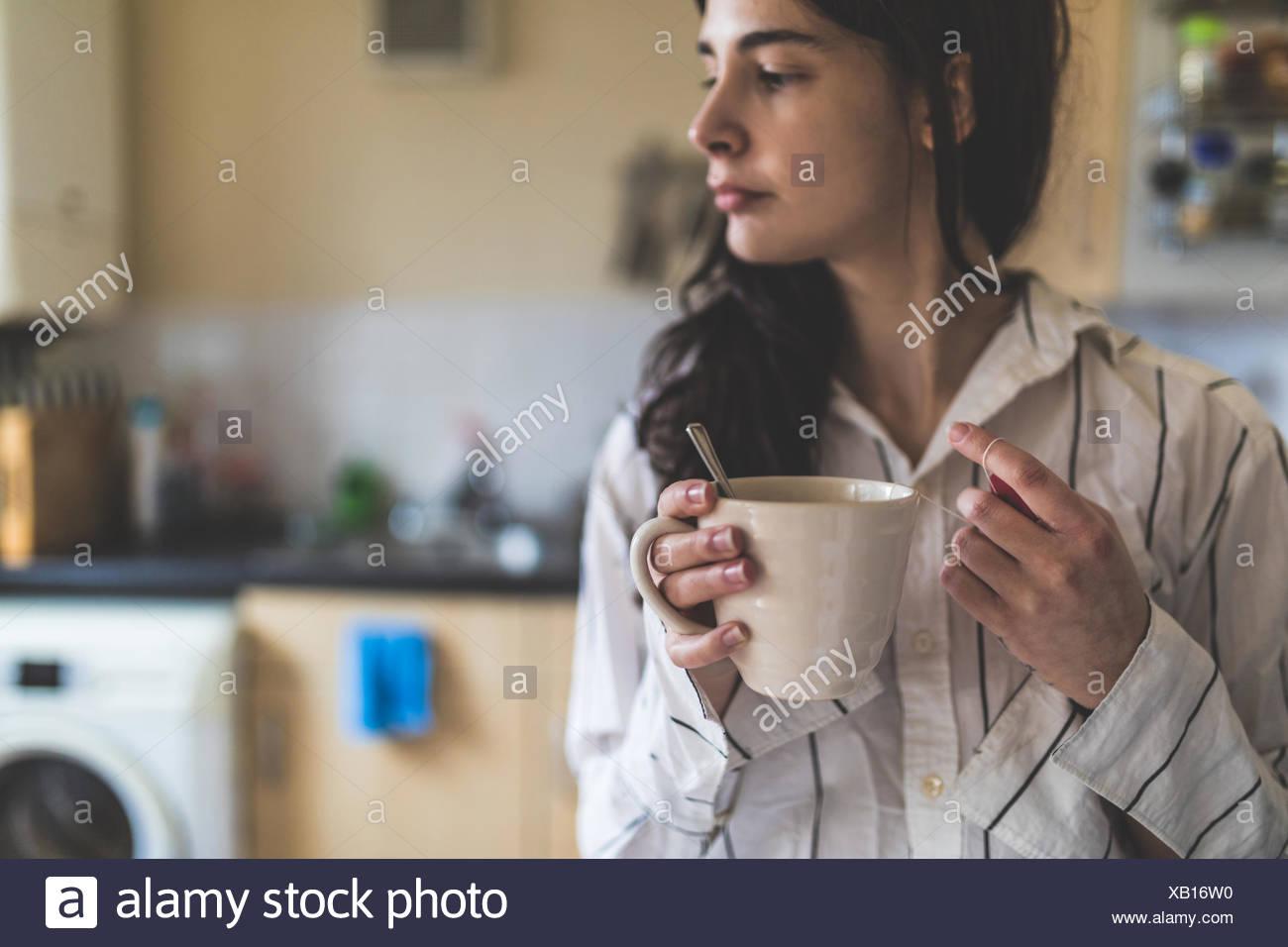 Junge Frau zu Hause tragen Schlafanzüge, halten Kaffeetasse Stockbild
