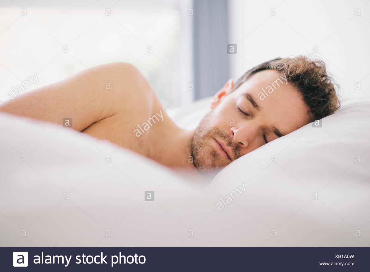 Junger Mann auf Seite schlafend im Bett liegend Stockbild