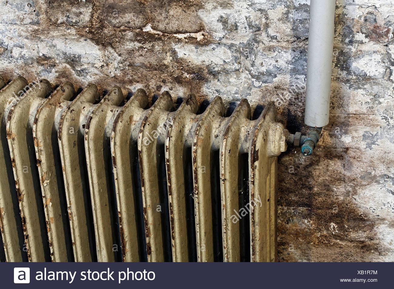 Alte Heizkorper Mit Farbe Abplatzt Montiert An Feuchten Kellerwand